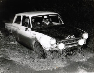 a Mk1 Cortina crossing a ford in a rally