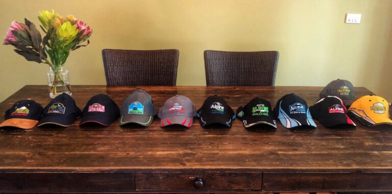 a row of 13 alpine rally caps